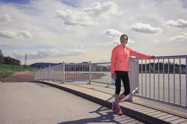 Female jogger having a break on a bridge - VTF000209