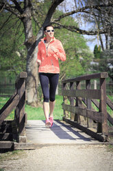 Woman jogging over a footbridge - VTF000204