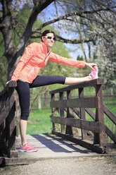 Woman stretching on a footbridge - VTF000203