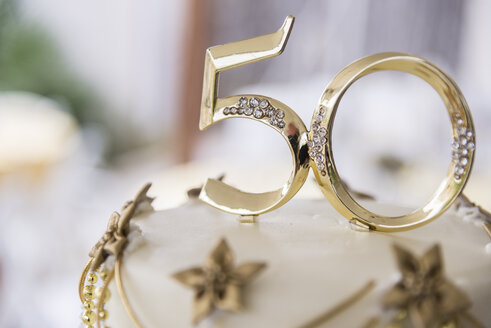 Number 50 in golden plastic attached to the top of a wedding anniversary cake - ABAF001314