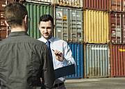 Businessman talking to teenager at container terminal - UUF000321