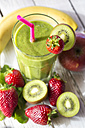 Glass of kiwifruit smoothie and fruits on wooden table - SARF000501