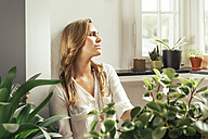 Germany, Bonn, Young woman sitting and pondering between her plants at home - MFF001006