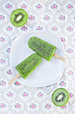 Two kiwi ice cream lollies on plate and two halves of kiwi, view from above - LVF001102