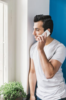 Portrait of young man telephoning with smartphone in his kitchen - MFF001021