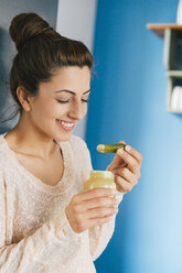 Portrait of young pregnant woman eating pickled gherkin with mustard in her kitchen - MFF000998