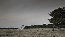 Germany, Bavaria, Froettmaning Heath, young woman wearing a tulle dress and running - FCF000045