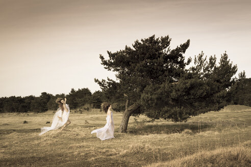 Germany, Bavaria, Froettmaning Heath, young women wearing a tulle dress and running and jumping - FCF000047