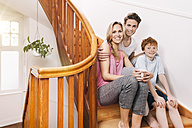 Happy family sitting on wooden stairs of their house - MFF001030