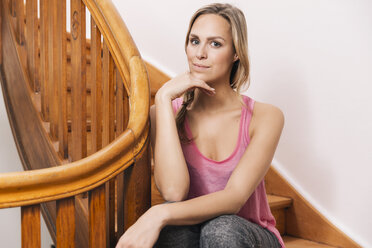 Portait of young woman sitting on wooden stairs of her house - MFF001027