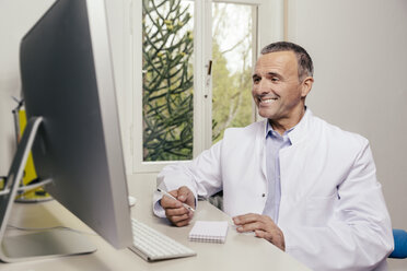Smiling doctor sitting at desk with computer - MFF001067