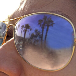Mirroring beach and palm trees on a pair of sunglasses, Fuerteventura, Spain - DRF000662