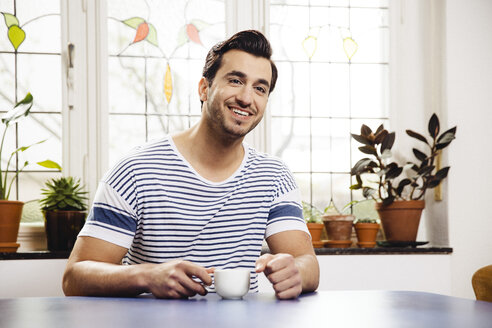 Portrait of happy young man sitting at blue table with a cup - MFF001043