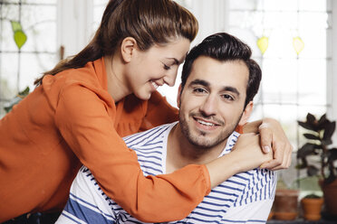 Happy young woman embracing young man at home - MFF001040