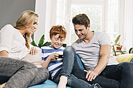Young family sitting on couch looking at smartphone - MFF001081