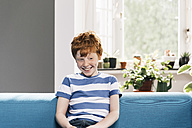 Boy sitting on blue couch in living room - MFF001079