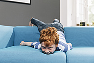 Boy rollicking around on blue couch in living room - MFF001071