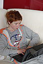Boy sitting on sofa using laptop - LB000692