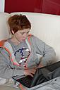Boy sitting on sofa using laptop - LB000692