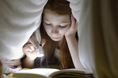 Portrait of girl reading a book secretly in bed under the blanket - LBF000694