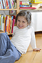 Smiling girl at home sitting on floor - LAF000797