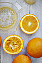 Oranges, halves of oranges and juice squeezer on grey wood, elevated view - KSWF001252