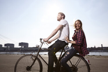 Happy couple riding bicycle on riverbank - FMKF001175