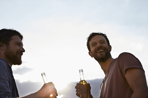 Two friends with beer bottles outdoors - FMKF001177