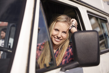 Smiling young woman in minivan - FMKF001233