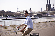 Man riding bicycle on riverbank - FMKF001193