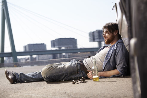 Man lying on ground leaning against car - FMKF001207