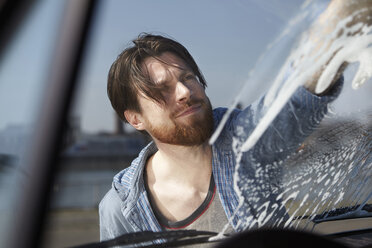 Man washing front window of a car - FMKF001210