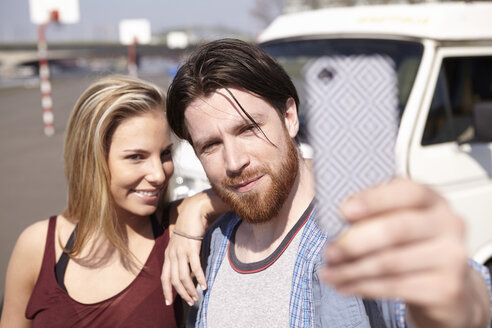 Man taking selfie with girlfiend in front of car - FMKF001213