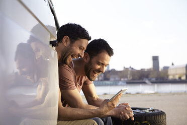 Two laughing men sitting in car looking at digital tablet - FMKF001235