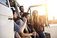 Happy friends celebrating at minivan - FMKF001238
