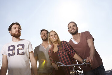 Four smiling friends with bicycle - FMKF001243