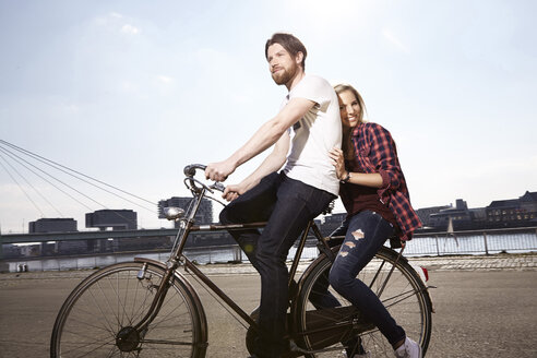 Happy couple riding bicycle on riverbank - FMKF001244