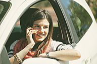 Spain, Barcelona, Young woman in car on cell phone - EBSF000222