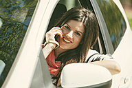 Spain, Barcelona, Young woman in car on cell phone - EBSF000225