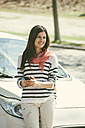 Spain, Barcelona, Young woman at car with cell phone - EBSF000229