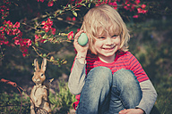 Boy in garden holding Easter egg - MJF000978
