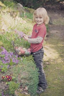 Boy in garden carrying Easter basket - MJF000986