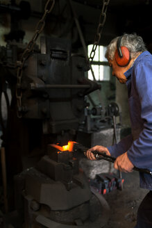 Germany, Bavaria, Josefsthal, blacksmith at work in historic blacksmith's shop - TCF003957