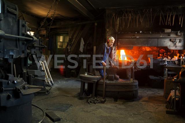 Germany, Bavaria, Josefsthal, senior blacksmith at work in historic blacksmith's shop - TCF003959