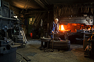 Germany, Bavaria, Josefsthal, senior blacksmith at work in historic blacksmith's shop - TCF003959