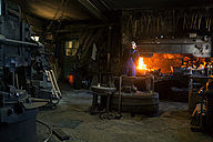 Germany, Bavaria, Josefsthal, senior blacksmith at work in historic blacksmith's shop - TCF003989