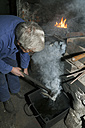Germany, Bavaria, Josefsthal, blacksmith at work in historic blacksmith's shop - TCF003971