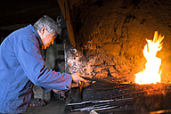 Germany, Bavaria, Josefsthal, blacksmith stiring fire at historic blacksmith's shop - TCF003975