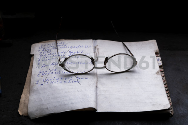 Germany, Bavaria, Josefsthal, opened order book and glasses in front of black background - TCF003979
