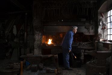 Germany, Bavaria, Josefsthal, blacksmith with glowing pickaroon at historic blacksmith's shop - TC003990
